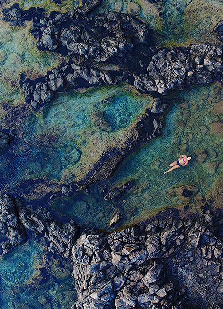 Cove with girl swimming in Oahua island in the Central Pacific